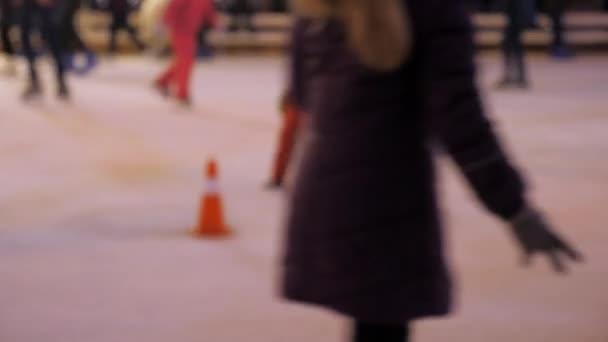 Defocus. Männer Frauen Kinder Schlittschuh laufen auf dem Eis im Winter. Menschen, die Amateursport betreiben