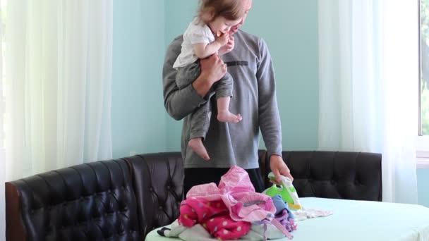 Padre e bambino. Stirare i vestiti dei bambini. Un uomo nel ruolo di genere non tradizionali. Assistenza bambini e lavori domestici