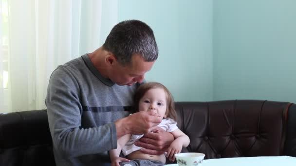 Padre tenta di imboccarlo bambino. Ruolo del papà casalingo