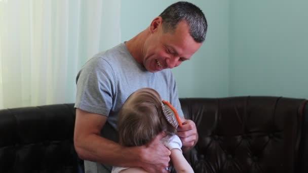 Capelli della figlia di papà pettinatura. Congedo di paternità. Un uomo di allevare un bambino
