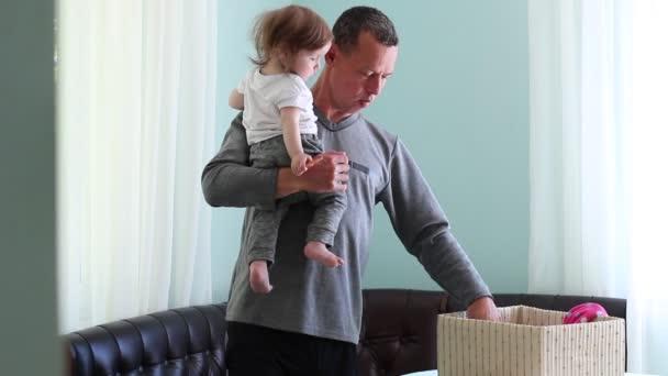 Paternità. Assistenza allinfanzia, lavori domestici e cucina. Un uomo nel ruolo di genere non tradizionali. Vestiti dei bambini di padre pieghe