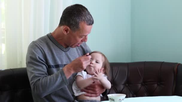 Un uomo nutre la figlia con i cucchiai. Paternità: prendersi cura di infante