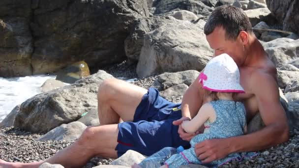Padre e figlia sulla spiaggia. Uomo con la bambina ha divertente si siede sulla spiaggia di ghiaia sotto le onde del mare Surf