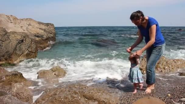 Madre e figlia sulla spiaggia. Primi passi del bambino sulla spiaggia rocciosa