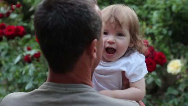 piccolo padre baciare ragazza. Padre felice con la figlia nel giardino