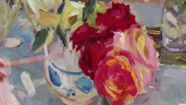 Close up of mans hand painting still life picture on canvas in art studio. Etude with oil paints