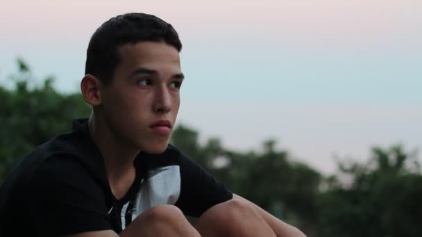Teen Boy Sits Alone Looking Sad Or Worried. Dejected Upset Young Man Sitting At Sunset. Evening city
