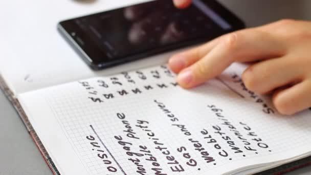 Měsíční rozpočet bydlení. Hospodyňka, pomocí vašeho smartphonu, se počítá vaše měsíční náklady na bydlení: hypotéka, daně, strata, nájemné, pojištění, nástroje