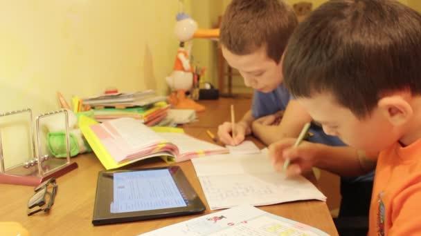 Dva bratři, dělá domácí práce a použití tabletového počítače