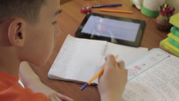 Studenti sedí u stolu studovat s Tablet psaní v poznámkovém bloku