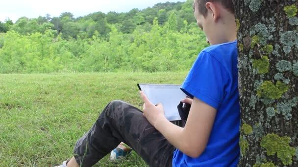 Mladý chlapec dělá domácí práce s tabletovým počítačem venku