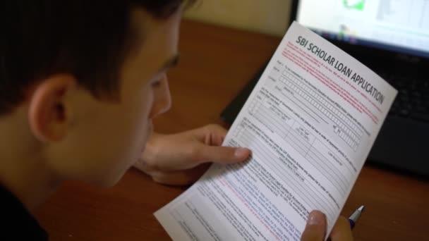 Mladý muž je podání žádosti o úvěr učenec Sbi. Úvěr formulář žádosti na listu papíru