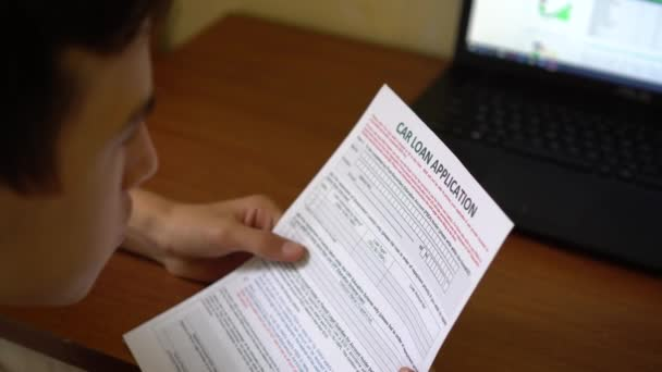 A young man is applying for a car loan. Credit application form on a paper sheet