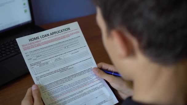 A young man is applying for a home loan. Credit application form on a paper sheet