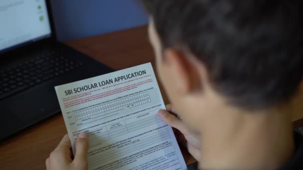 A young man is applying for a SBI scholar loan. Credit application form on a paper sheet