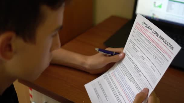 A young man is applying for a student loan. Credit application form on a paper sheet