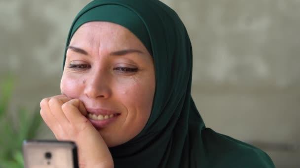 moderne glückliche muslimische Frau im Hijab mit Smartphone-Look, blättert durch Social-Media-Feed auf Smartphone, kichert und lächelt von Nachrichten über Anwendungen