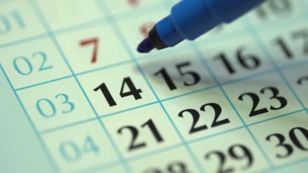 Čtrnáctý den v měsíci. Žena označí datum v kalendáři modrou značkou. Plánovač a organizátor kalendáře obchodních stěn