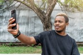 Close up of dark-skinned man in black T-shirt making selfie on mobile phone.