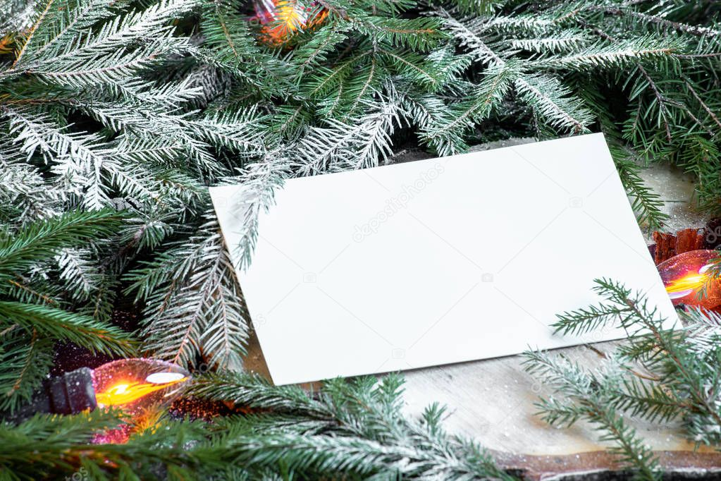 Blank envelope on christmas tree branches, new year decoration and garland.