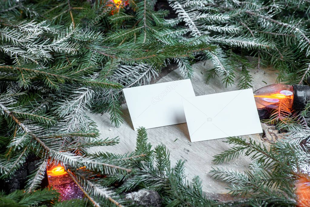Blank business cards on christmas tree branches, new year decor and garland.