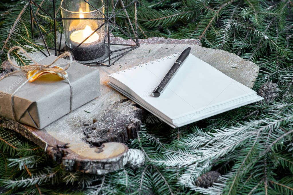 Blank notepad with christmas tree branches, new year decoration and gift boxes.