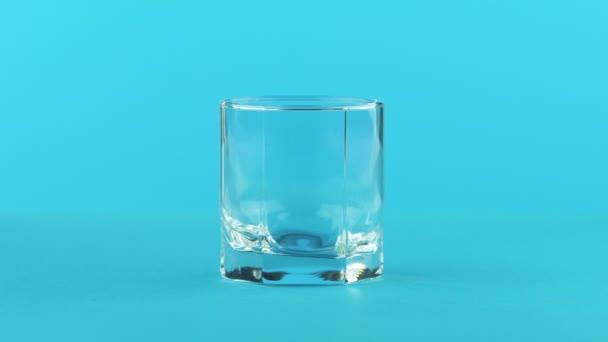 4 k close-up shot z mléka studeného nápoje pít pooring do nízké sklenice s fasetami modré pozadí ve studiu