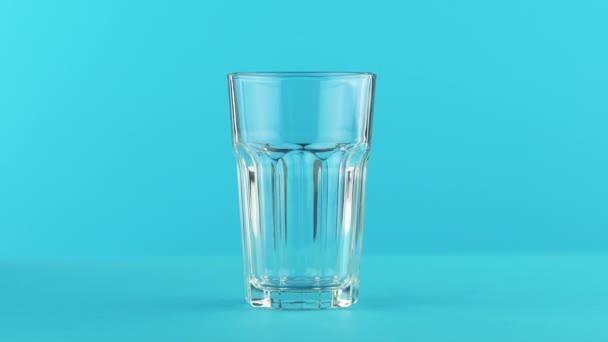 4 k close-up shot z mléka studeného nápoje pít pooring do broušeného skla v barevném modrém pozadí ve studiu