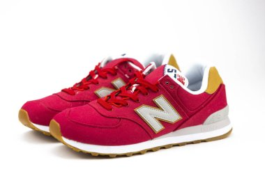 BOSTON, MA, USA, January 2019 - Red New Balance NB 574 athletic shoes on studio background. New Balance Athletics one of the worlds major sports footwear manufacturers. Illustrative editorial