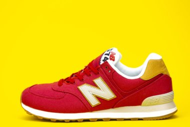 BOSTON, MA, USA, January 2019 - red New Balance NB 574 athletic shoes on yellow studio background. New Balance Athletics one of the worlds major sports footwear manufacturers. Illustrative editorial