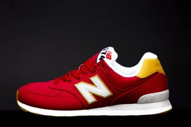 BOSTON, MA, USA, January 2019 - Red New Balance NB 574 athletic shoes on black studio background. New Balance Athletics one of the worlds major sports footwear manufacturers. Illustrative editorial