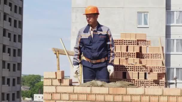 Minsk, Bělorusko, Srpen 14 2018-Builder staví bytové výstavby cihel. Pracovník na staveništi klade cihly. Brickwork průmyslová