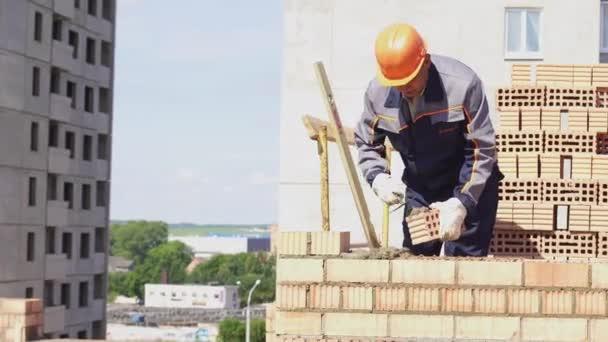 Minsk, Bělorusko, Srpen 14 2018-stavba bytové výstavby cihel. Pracovník na staveništi klade cihly. Brickwork průmyslová