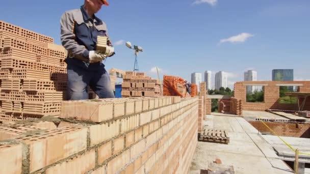 Minsk, Bělorusko, Srpen 14 2018-vybudování bytové výstavby cihel. Pracovník na staveništi klade cihly. Brickwork průmyslová