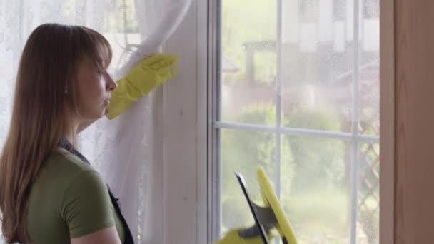 Žena v domácnosti rozstřikuje čistič oken a myje okno skleněným stěračem
