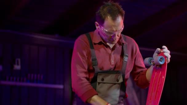 Handwerker mit Schutzbrille repariert Skateboard oder Wimpelbrett in seiner Werkstatt.