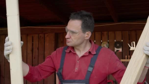 Tischler hält zwei polierte Holzbalken in den Händen und vergleicht ihre Größen