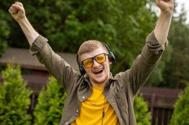 Joyful smiling man in headphones listen positive music outdoors, winner concept