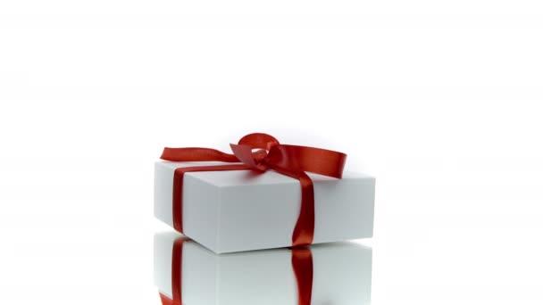 Gyönyörű fehér ajándék doboz piros íj forgó elszigetelt fehér háttér
