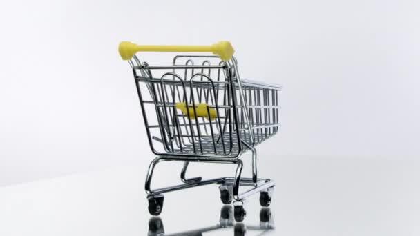 prázdný nákupní košík odražené ve skleněném povrchu 360 rotující na bílém pozadí