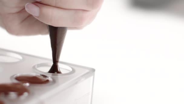 Chocolatier gießt geschmolzene Schokolade in Bonbonform für handgemachte Bonbons slow mo