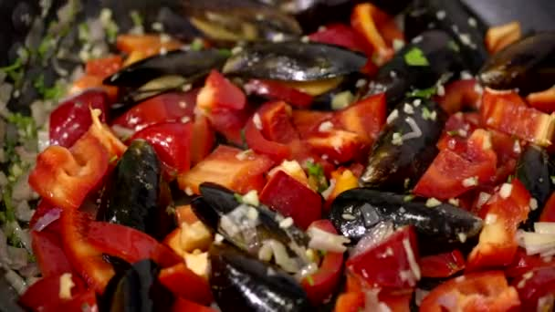 Close-up vegetables and mussels fried in skillet with steam, preparing paella