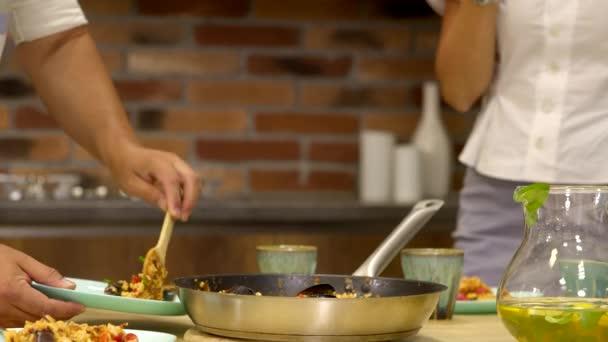 A közeli tálalóasztal tányérokon tálalja a házi készítésű ételt, családi főzés