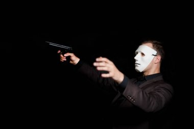 A man in a white mask falls from a gunshot wound with a pistol i