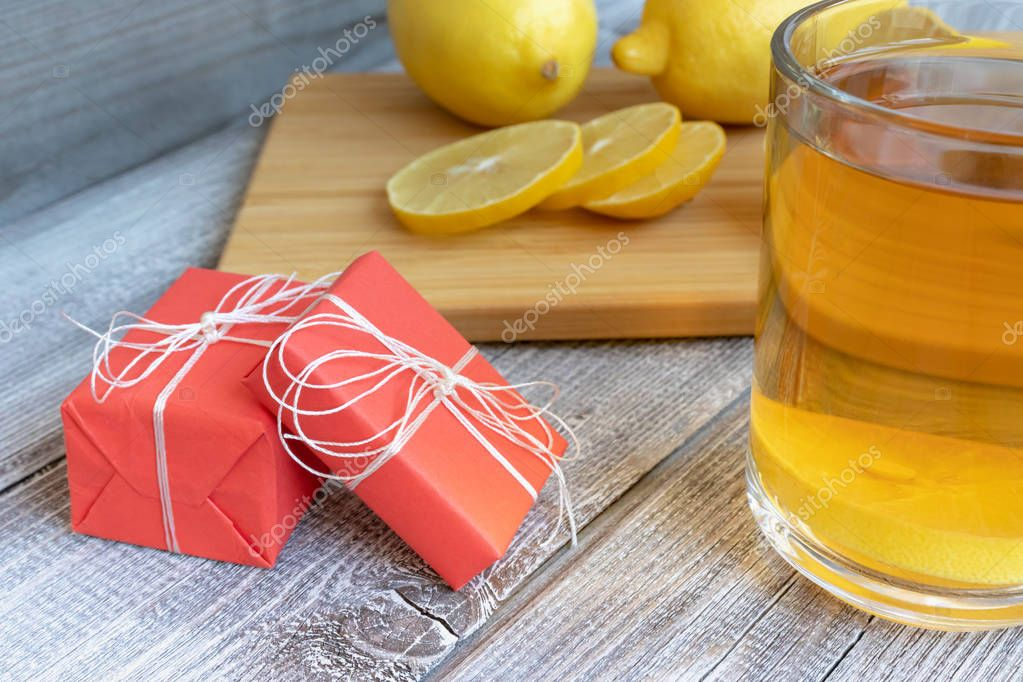 Tea with lemon on a wooden table, holiday present boxes and pieces of diced lemon.