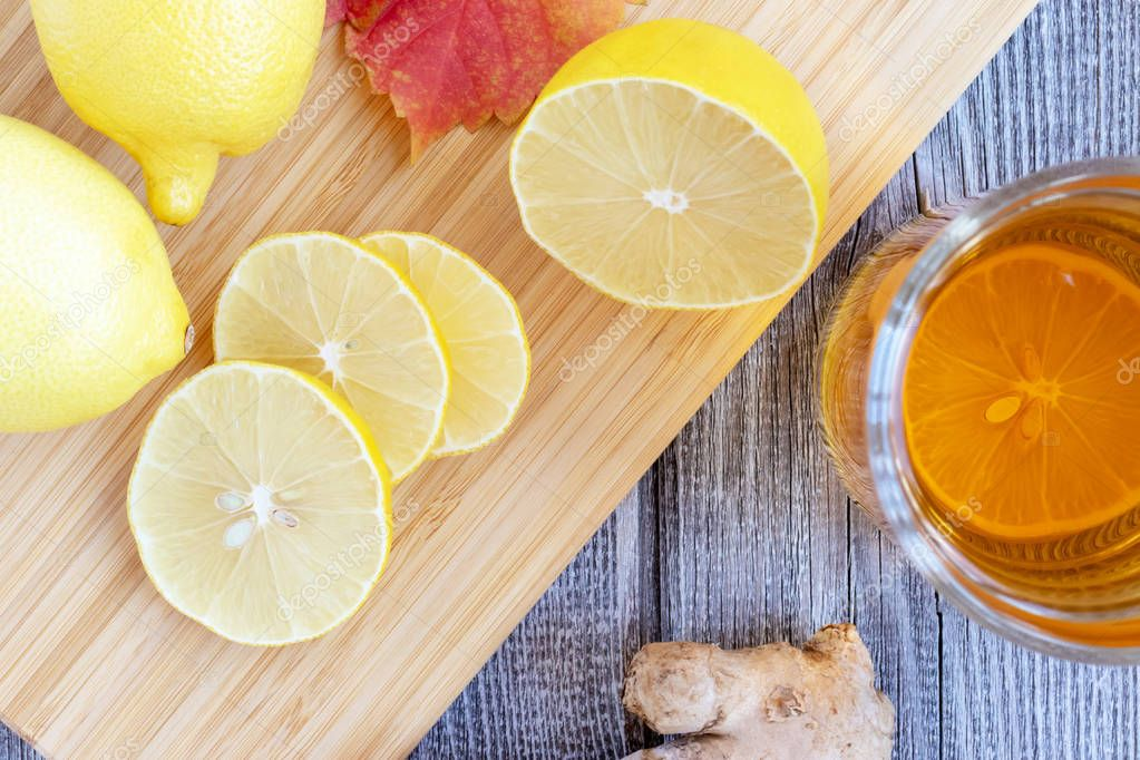 Ginger tea with lemon on a wooden table and pieces of diced lemon.