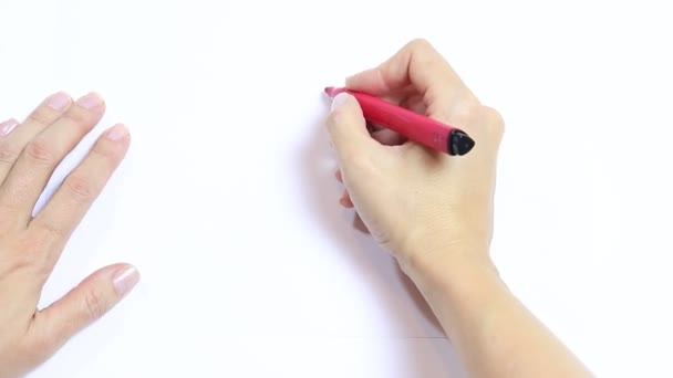 Womans hand drawing red heart with marker on white table