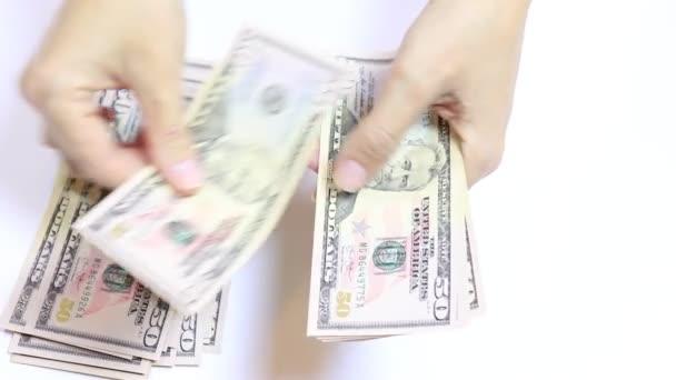 Slowmo video z ženských rukou počítání peněz na bílém, hotovosti padesát dolarové bankovky zblízka