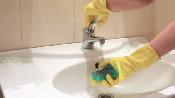 Unrecognizable woman in yellow rubber gloves washing a sponge with water in bathroom sink. Cleaning and washing concept