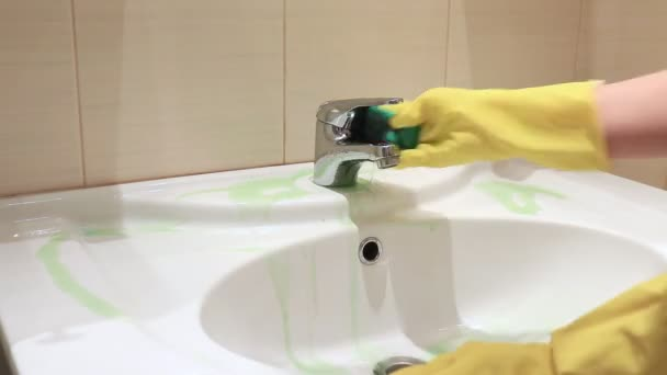 Unrecognizable woman in yellow rubber gloves washing dirty bathroom sink with a green sponge. Cleaning and washing concept